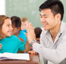 volunteer helping student in classroom